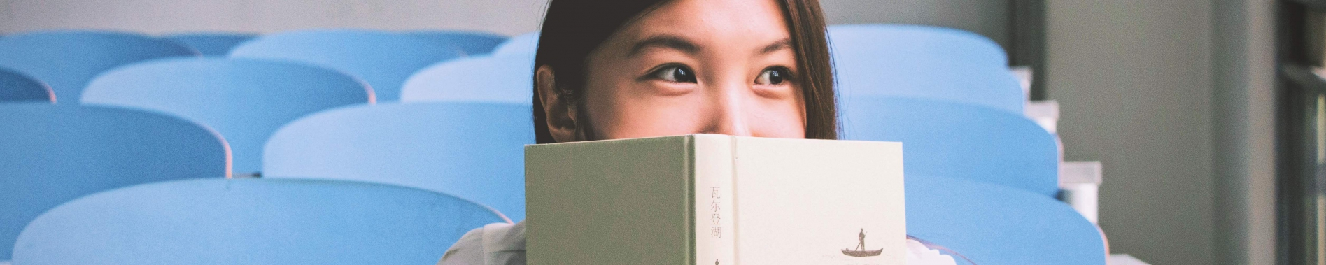 young student sitting in an empty classroom hiding her bottom part of face behind a book