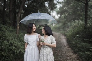 Two girls walking in a park under a white umbrella