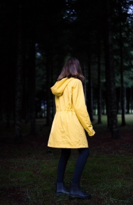 Woman with yellow rain jacket from the back walking in a park